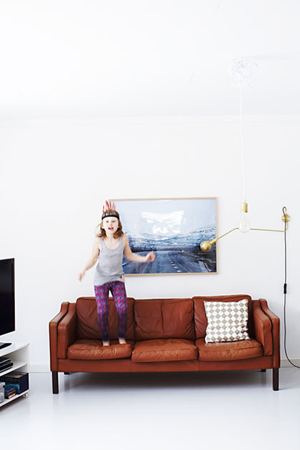 Girl jumping in a sofa.