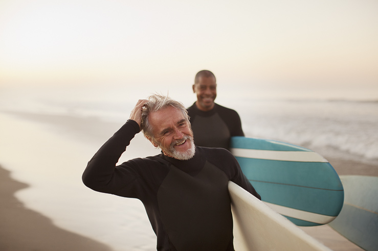 Image-ID: cai412-01281, Older surfers carrying boards on beach